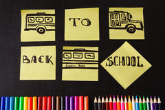 Back to school background with a lot of colorful felt-tip pens and colorful pencils, titles `Back to school`. And drawing of school bus drawn on the yellow Royalty Free Stock Photos