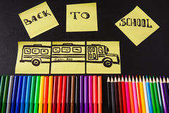 Back to school background with a lot of colorful felt-tip pens and colorful pencils, titles `Back to school`. And drawing of school bus drawn on the yellow Stock Image