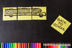 Back to school background with a lot of colorful felt-tip pens and colorful pencils, titles `Back to school`. And drawing of school bus drawn on the yellow Stock Photos
