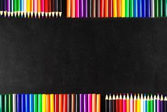 Back to school background with a lot of colorful felt-tip pens and colorful pencils on the black scratched chalkboardn Stock Photography