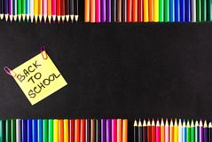 Back to school background with a lot of colorful felt-tip pens and colorful pencils, titles Back to school on the yellow Royalty Free Stock Photography
