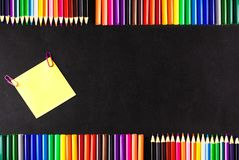 Back to school background with a lot of colorful felt-tip pens and colorful pencils,  the yellow piece of paper o Stock Photography