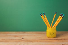 Back to school background with pencils in emoji jar on wooden table. Over green wall royalty free stock photo