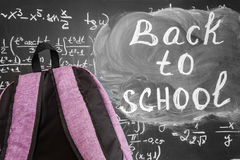 Back to school background with purple school bag  and the title `Back to school` and math formulas written by white chalk. On the black school chalkboard Stock Images