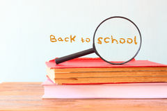 Back to school background with stack of books and magnifying glass Royalty Free Stock Photo