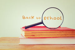 Back to school background with stack of books and magnifying glass. filtered image Royalty Free Stock Photo