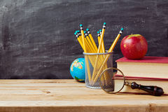 Back to school background with teachers objects over chalkboard. And wooden table Royalty Free Stock Photography