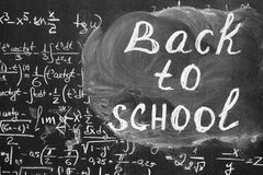 Back to school background with title `Back to school` and math formulas are written by white chalk on the black chalkboard. Stock Images