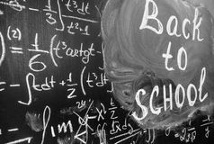 Back to school background with title `Back to school` and math formulas are written by white chalk on the black chalkboard. Stock Photography