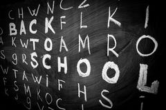 Back to school background with title `Back to school` among other letters of English alphabet written by white chalk Stock Images