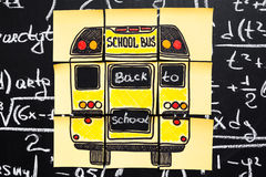 Back to school background with title `Back to school` and `school bus`  written on the yellow pieces of paper on the  chalkboard. With math formulas written by Royalty Free Stock Photography