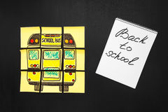 Back to school background with title `Back to school` and `school bus` written on the yellow pieces of paper and notebook. With title `Back to school` are on Stock Photography