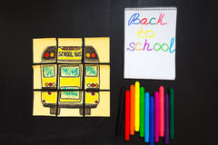 Back to school background with title `Back to school` and `school bus` written on the yellow pieces of paper, notebook with title. `Back to school` and colorful Royalty Free Stock Images