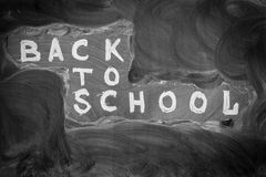 Back to school background with title `Back to school`  written by white chalk on the black chalkboard and chalky stains. From erasing Stock Photo