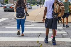 Back to school - the backs of college students crossing urban crosswalk with backpacks - ethnic diversity and casual dress with ca. Rs driving by stock images