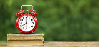 Back to school banner. Back to school- website banner of a red alarm clock on old books Royalty Free Stock Photos