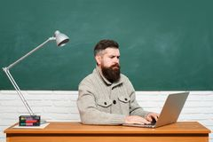 Back to school. Bearded teacher in education class near chalkboard. Tutor. Education and learning people concept. Preparing for exam in college. Blackboard for stock photography