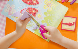 Back to school!. Beautiful little girl cutting paper with scissors on the art lesson class. Children education concept. Kids crafts Royalty Free Stock Images