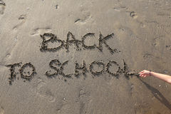 Back to School big written on the beach. With child hand Royalty Free Stock Image
