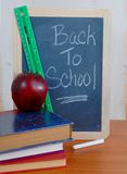 Back to School. Black board with Back to School message with green ruler, red apple, white chalk and some books stacked on a table. Rough, rustic wood background stock photography