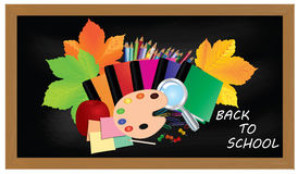 Back to school. Black desk with school supplies and autumn leaves. Royalty Free Stock Photography