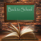 Back to school blackboard on brick wall. With open old book Royalty Free Stock Photography