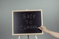 Back to school blackboard, chalkboard. Teacher writing back to school on black chalk board Stock Photos