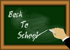 Back to school on blackboard with hand Royalty Free Stock Photo