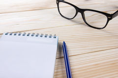 Back to school. Blank note pad, notebook with pen and glasses Stock Images