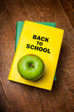 Back to School book with an apple. Stack of books with a yellow book cover with Back to School and a green apple sitting on top of the book on a wooden desktop Royalty Free Stock Photography
