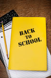 Back to School book with notepad. Yellow Back to School book cover with a pencil, ruled notedpad and compostition book on a wood desktop Stock Photography