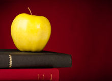 Back to School Books with Apple. School Books stacked with an apple on top, a red background and space on the right for your text royalty free stock image