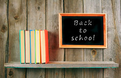 Back to school. Books on wooden shelf and frame. Stock Photos