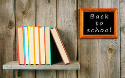 Back to school. Books on wooden shelf and frame. Royalty Free Stock Photos