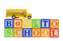 Back to School Bus Blocks. Back to School spelled out in wooden alphabet blocks with miniature yellow school bus on top Royalty Free Stock Images