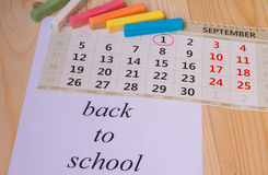 Back to school, calendar, colored chalk on wooden background Royalty Free Stock Photography