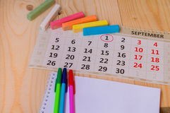 Back to school, calendar, colored chalk on wooden background Royalty Free Stock Image