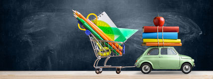 Back to school car. Back to school sale background. Car delivering shopping cart with accessories, books and apple against blackboard Stock Photography