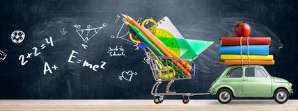 Back to school car. Back to school sale background. Car delivering shopping cart full of accessories, books and apple against blackboard with education symbols Royalty Free Stock Image