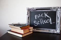 Back to school, chalk in a vintage frame. Text on chalkboard and a stack of textbooks stock image