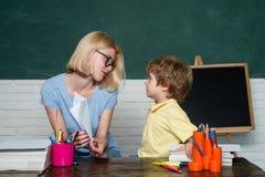 Back to school. Child and teacher near chalkboard in school classroom. Great study achievement. School lessons. stock photo