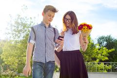 Back to school, Children teenagers go first day to school, with bouquet of flowers, smile, talk. Back to school, Children teenagers go first day to school, with royalty free stock image