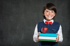 Back to school. Closeup of little boy holding stack of books and apple. Happy schoolboy smiling and looking at camera. Cheerful child holding books with red Stock Photos