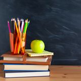 Back to School cocept. Still life with school books, pencils and. Apple against blackboard background. Close up stock photo
