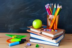 Back to School cocept. Still life with school books, pencils and. Apple against blackboard background. Close up royalty free stock photos