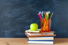 Back to School cocept. Still life with school books, pencils and. Apple against blackboard background. Close up stock photos