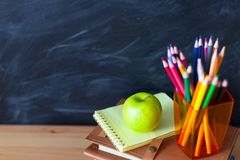 Back to School cocept. Still life with school books, pencils and. Apple against blackboard background. Close up stock images