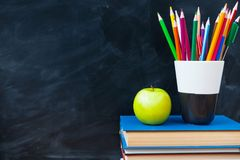 Back to School cocept. Still life with school books, pencils and. Apple against blackboard background. Close up royalty free stock image