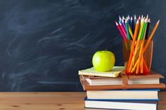 Back to School cocept. Still life with school books, pencils and. Apple against blackboard background. Close up royalty free stock images