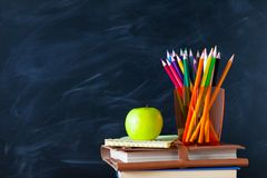 Back to School cocept. Still life with school books, pencils and. Apple against blackboard background. Close up royalty free stock photo